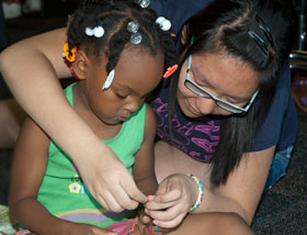volunteer helps child with bead craft