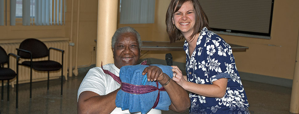 A GRHC Resident Services Specialist awards a door prize to a resident during a special event