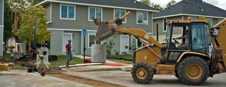 construction worker operates a backhoe in construction site