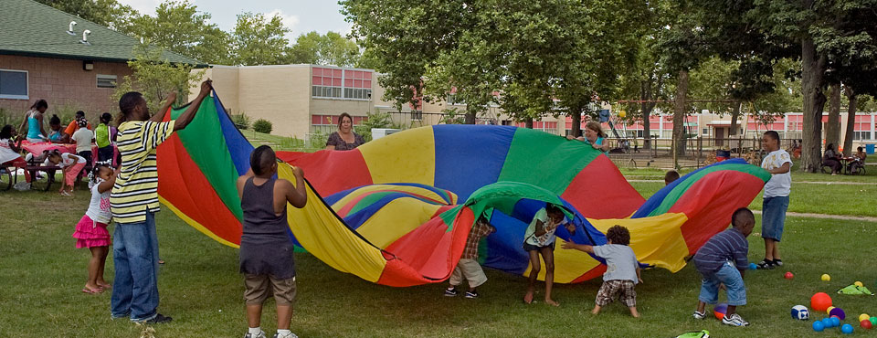 families playing outdoors with giant parachute