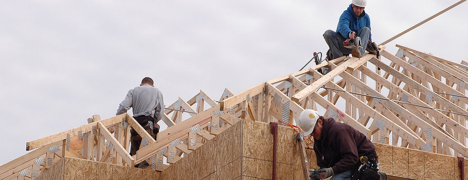 three construction workers framing roof of duplex unit